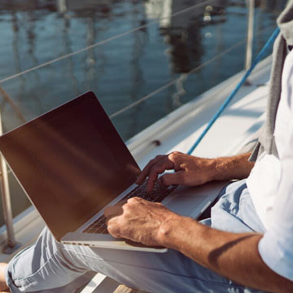 Man with laptop sitting by sea